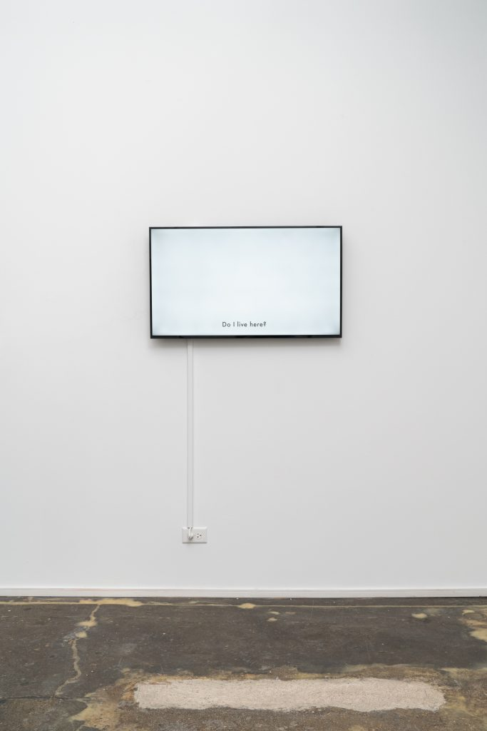 "Jazmine Harris, Re-membering (lobby conversations), 2020, HD single-channel video. Screen mounted on exhibition wall is white, with the text, ""Do I Live Here?"" Photo courtesy of the artist and curator."