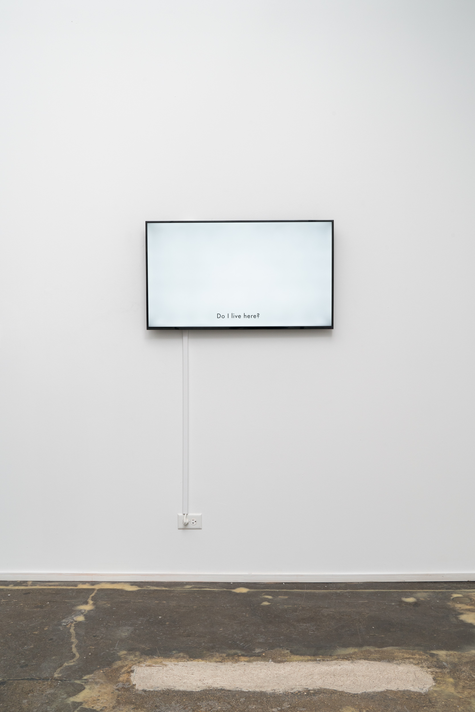 """Jazmine Harris, Re-membering (lobby conversations), 2020, HD single-channel video. Screen mounted on exhibition wall is white, with the text, """"Do I Live Here?"""" Photo courtesy of the artist and curator."""
