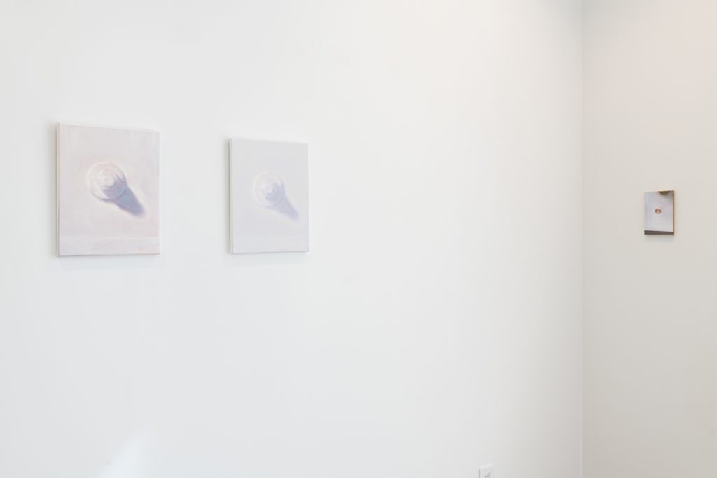 Image: Brendan Getz, installation view of Usual Objects. (l) Painted building bolt and a barycentric view, 2021. Oil on stretched canvas, 14 x 11 inches, each. (r) penny painting and the counter plane, double glint in the window light, 2021. Oil on clayboard, 7 x 5 inches. Image courtesy of the artist and Carrie Secrist Gallery.