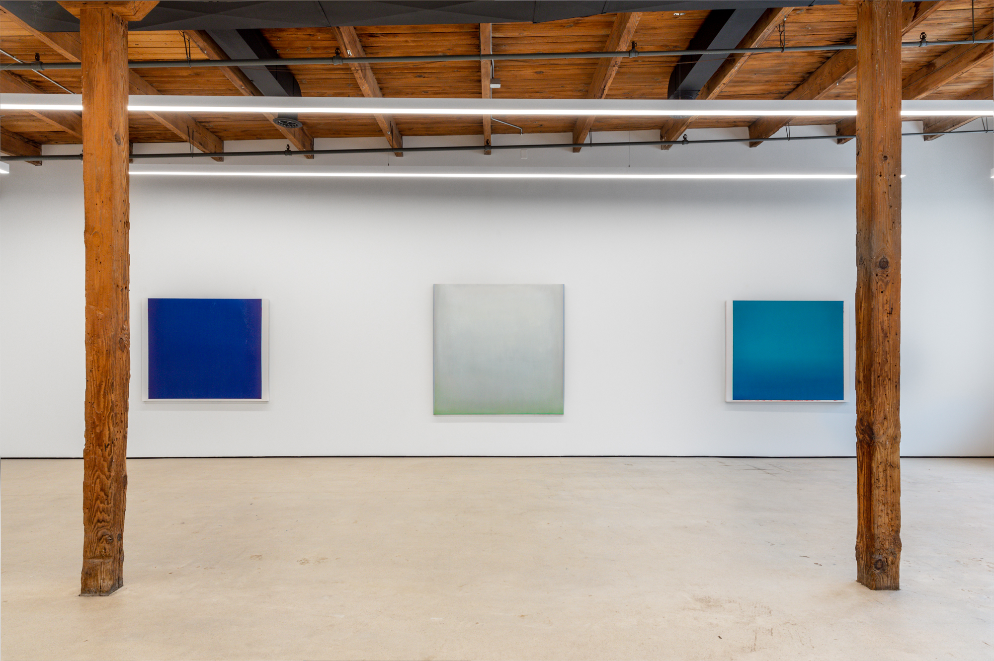 Featured image: An installation view of Sergio Lucena: The Blue that embraces me... at Mariane Ibrahim Gallery. Three paintings hang on a white wall. Photo by Evan Jenkins, Courtesy Mariane Ibrahim.