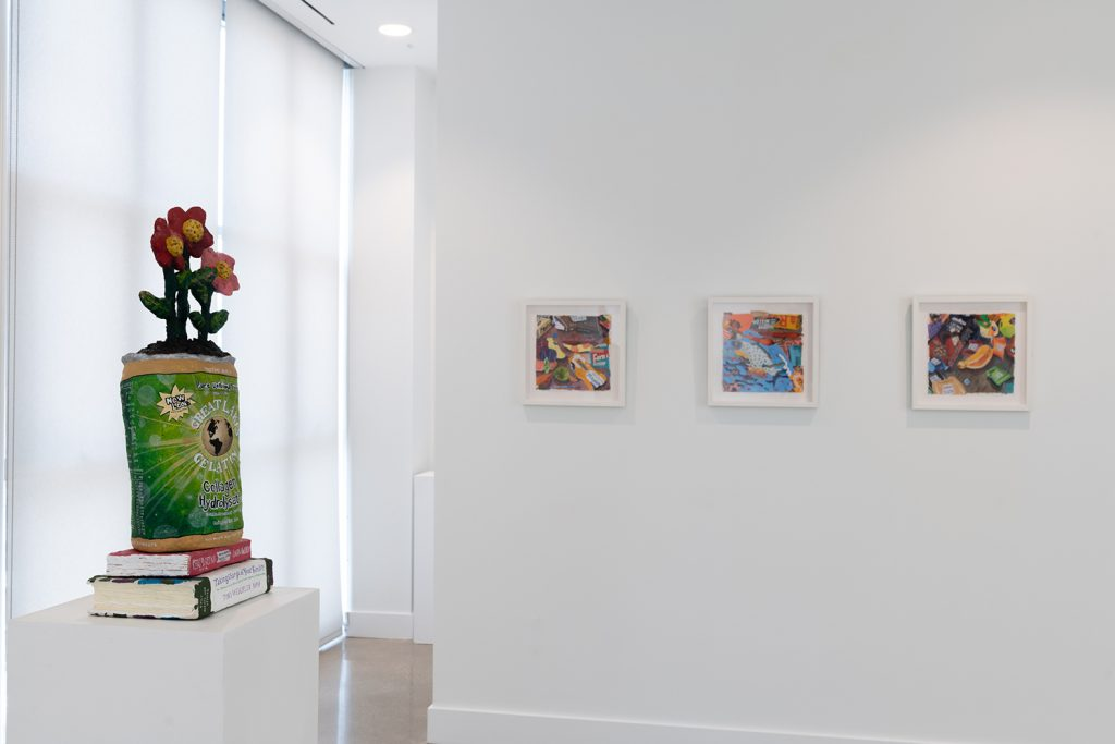 Image: Nicole Dyer, installation view of Usual Objects. From left to right: Great Lakes Collagen, 2019. Acrylic, paint marker, ink, Papier-mâché, cardboard, insulation foam, dowel. 29 x 11 x 8 inches. Mayonnaise, 2019. Acrylic, watercolor, candy wrappers, pen, glitter, stickers, collage, and handmade polymer clay candies on handmade paper, 12 x 12 inches. Fish, 2019. Acrylic, watercolor, candy wrappers, pen, glitter, stickers, collage, and handmade polymer clay candies on handmade paper, 12 x 12 inches. Crema, 2019. Acrylic, watercolor, candy wrappers, pen, glitter, stickers, collage, and handmade polymer clay candies on handmade paper, 12 x 12 inches. Image courtesy of the artist and Carrie Secrist Gallery.