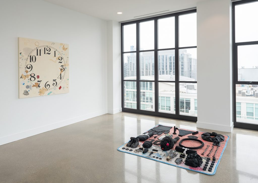 Image: Amanda Ross-Ho, installation view of Usual Objects. (l) Untitled Timepiece (ORAL ARGUMENTS/OVERLAPPING JURISTICTIONS), 2019-2021. Gesso, silkscreen, acrylic, ink, ball point pen, graphite, oil pastel, coffee, tea, paper, artist's tape, painter's tape, laser prints, stretch sequin fabric on canvas covered panel, 52 x 52 x 1.5 inches. (r) Untitled Seizure (ENCORE/DARK MATTER), 2021. Unfinished Black Glove (small), empty thread spool (UNTIRLED PERIOD PIECE), Extra Thong (ONCE YOU GO BLACK), facemasks, Giant Scrunchie (MY PEN IS HUGE), Cut and bundled pant legs (Untitled Production Line (Modern Times), black mouse, BLACK GLOVE FINGERTIP, Mouse (Yin), BINARY (Rubber Band), BINARY (Bobby Pin (3)), 10, Untitled Metrics (TENS), cut and bundled pants parts (Untitled Production Line (Modern Times),Nike Air Force Ones (UNTITLED PERIOD PIECE), Bundled and pinned canvas (Untitled Production Line (Modern Times), Black Earring (Untitled Peripheral Swatch (FOOTPRINTS AND FREE RADICALS)), pinned canvas (Untitled Production Line (Modern Times), Dead Brushes (Periphery Composition with Basket of Dead Brushes), satin scrunchie, Delta eyemask, canvas spaghetti (Untitled Production Line (Modern Times), vintage clock numbers, pinned canvas pucks (Untitled Production Line (Modern Times), Buttons Large (Untitled Production Line (Modern Times), Black Nitrile Glove, Rolled canvas (Untitled Production Line (Modern Times), Black 3D Printed Plastic silverfish (Untitled Production Line (Modern Times), Clock hands (Untitled Production Line (Modern Times), Buttons Small (Untitled Production Line (Modern Times), 77 x 67 x 5 inches. Image courtesy of the artist and Carrie Secrist Gallery.