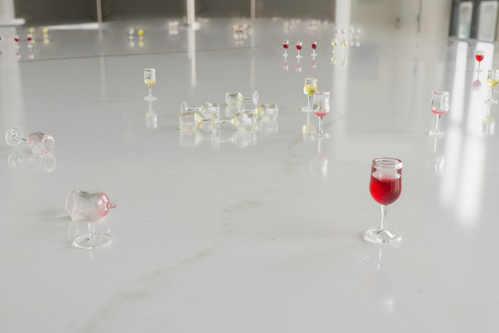 Image: Amanda Ross-Ho, installation view of Usual Objects. Untitled Opening (NOIR AND BLANCO). 2015. Thirty-five 1:12 scale glass wine glasses, pigmented resin, dimensions variable. Image courtesy of the artist and Carrie Secrist Gallery.