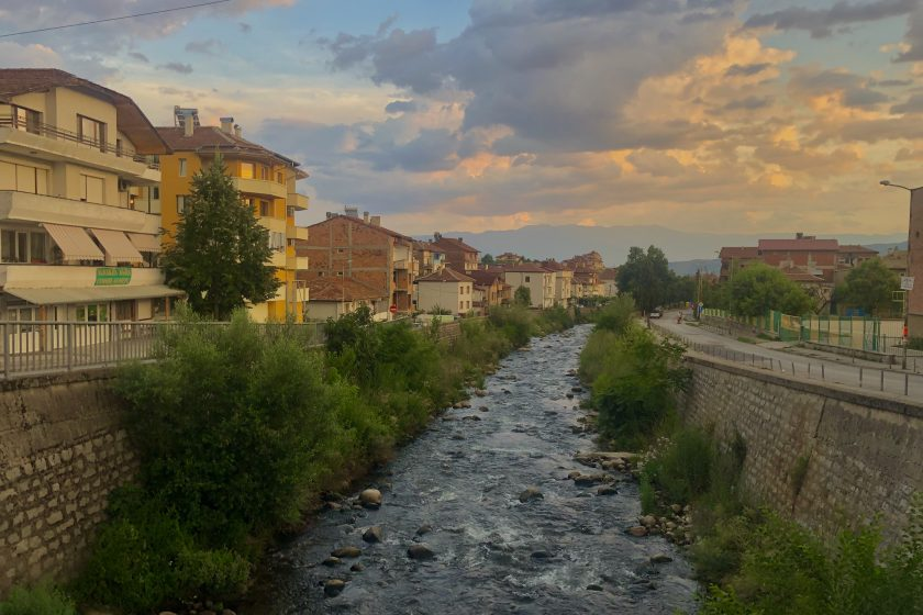 Featured image: A photograph of the Struma river, which cuts through the middle of the image (and also through the middle of Sandanski, Bulgaria), flanked by levees on either side. The water level is pretty low, so there is vegetation growing along the levees. On the left side of the river is a street and apartment complexes. On the right there is a street beyond which the edges of a school yard are visible. There is a mountain range visible in the distance. Photo by the author.