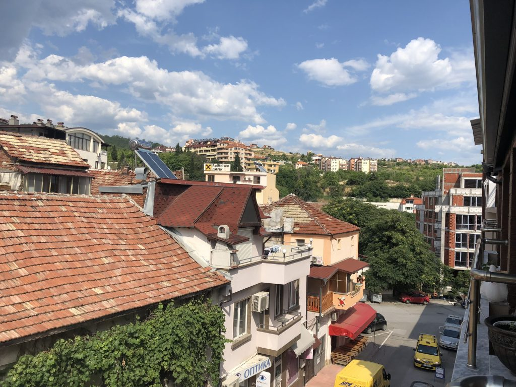 """Image: A photo overlooking a small section of Sandanski as seen from the terrace of an apartment. The traditional brick rooftops are on the left.. The facade of the first building from the left is obstructed entirely by grape vines. The second building is white and has a sign that says """"ОПТИКА,"""" roughly translated to """"optics"""" (it is an optometrist office). The third building is a peach color and the first level appears to be a small outdoor cafe. There are cars parked on the street below. There is a building still under construction on the right - only the brick framework is complete. Lots of greenery and trees break up the individual buildings and it's a bright summer day. Photo by the author."""
