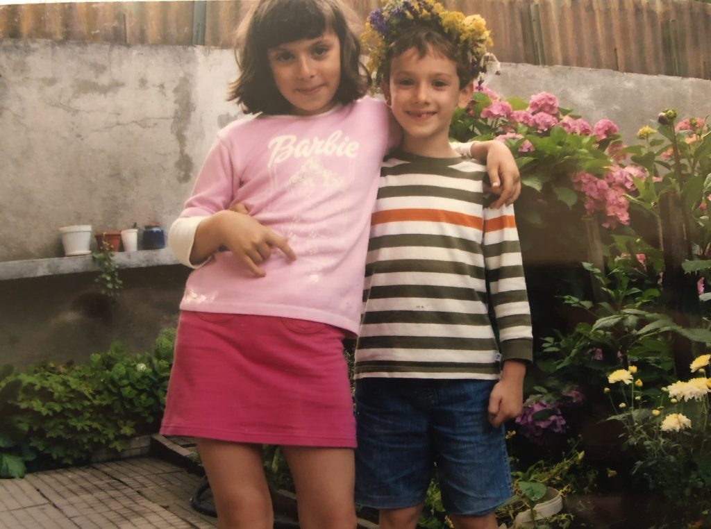 """Image: A photo in a photo album of the author and her brother when they were children. They are standing in a sideways embrace in the yard of their grandmother's house. There is a stone wall behind them and lots of flowers on the right. The author wears a light pink """"Barbie"""" long sleeve shirt and a magenta skirt. She has one hand slung around her brother. She has shoulder length brown hair and smiles at the camera. Her brother also smiles and is wearing a flower crown comprised of yellows and purples.. He wears a horizontally striped green, white, and orange long sleeve shirt and jean shorts. One hand is around his sister. Image courtesy of the author."""