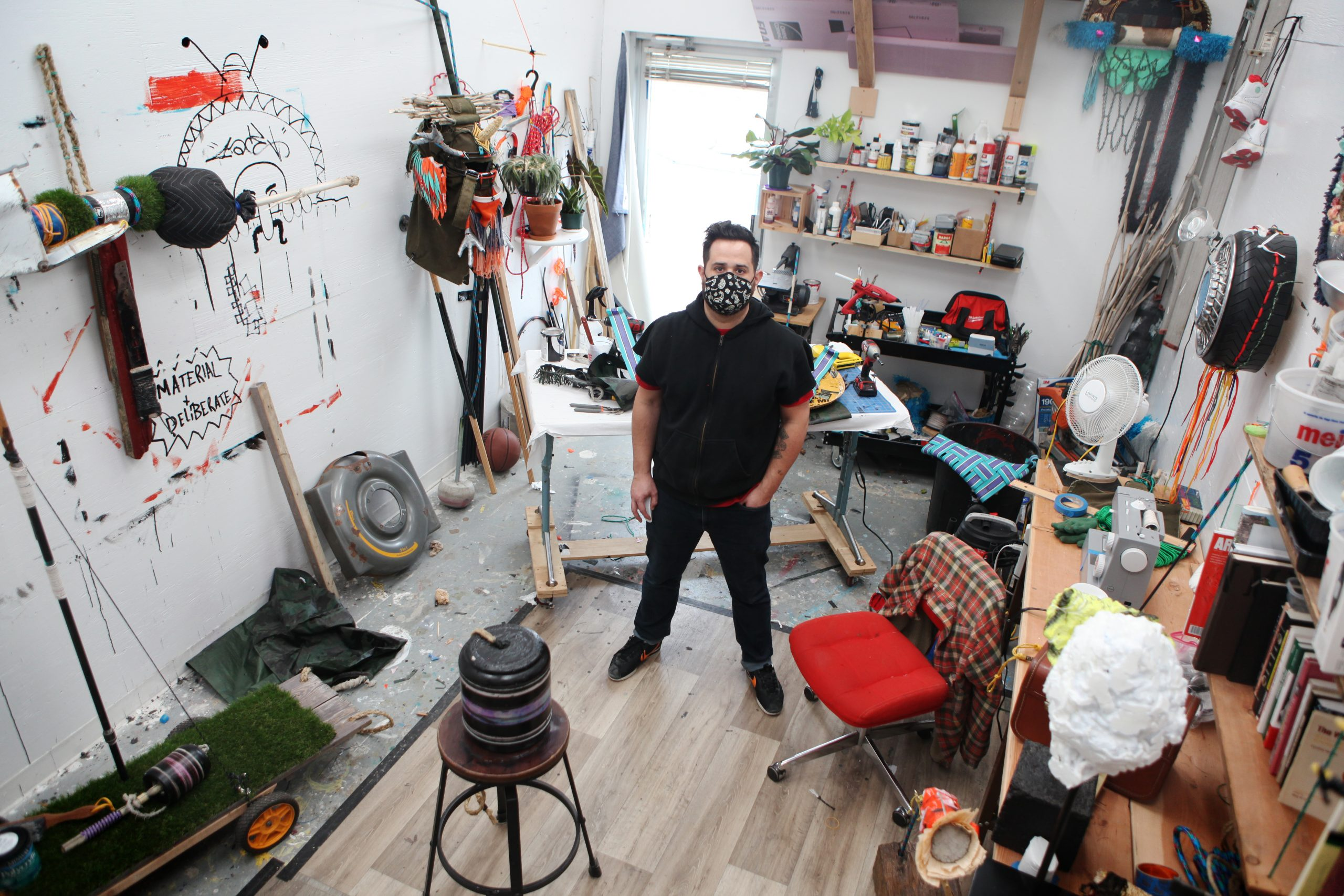 Featured Image: Stephen Signa-Aviles stands in his studio at the University of Illinois at Urbana-Champaign. He is wearing dark jeans and a dark, short-sleeved hooded sweatshirt, and a black face mask with a white graphic pattern. He looks up and into the camera. His studio space is narrow and cluttered. There are various works in progress, as well as shelving units with paints, books, and other materials. Photo courtesy of Stephen Signa-Aviles.