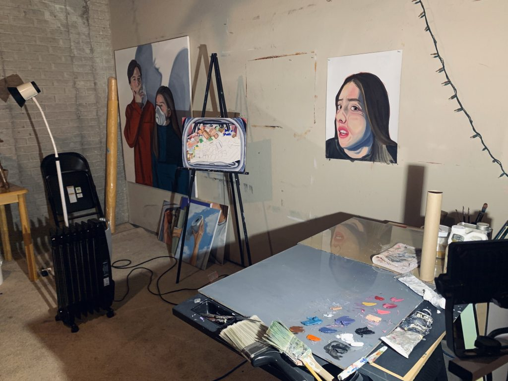 Image: A view of Pascale Grant's studio work space in the basement of her home. On a neutral, drywalled basement wall are two paintings. There is a small stack of paintings on the floor leaning against the wall. A painting in progress is on an easel between the two wall-hung works. On the right of the image is a table with paint palettes, brushes, and other painting supplies. On the left of the image are a space heater, a tall lamp, and a folding chair leaning on an unfinished wall. Photo courtesy of Pascale Grant.