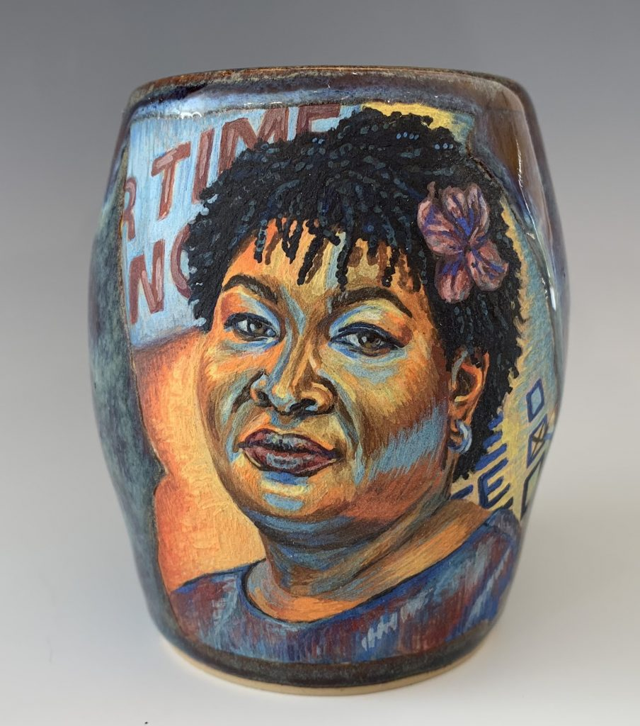 Image: Cristal Sabbath, Stacey Abrams, 2021, stoneware with underglaze watercolors and cone 6 glaze. A vessel with a vibrant portrait of Stacey Abrams. Photo by  Jonathan Castillo. Courtesy of Glass Curtain Gallery.