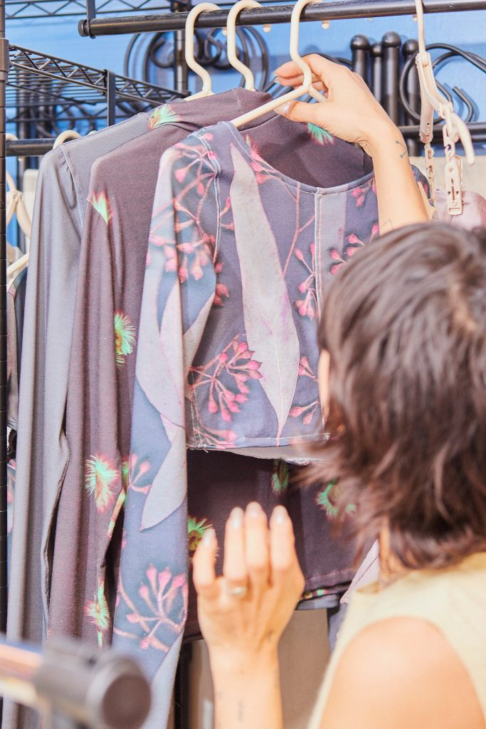 Image: Marissa Macias faces away from the camera looking at her clothing. Marissa is hanging a top on a rack where several other tops hang. The tops are mostly pale purple. Photo by Sarah Joyce.