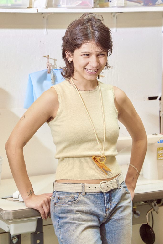 Image: Marissa Macias looks away from the camera while smiling and leaning against her sewing table. She is wearing jeans, a white belt, and a pale yellow shirt. Photo by Sarah Joyce.