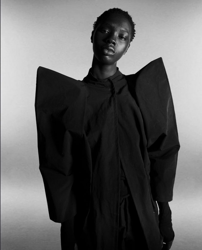 Image: A black and white image with model, at center, wearing a dramatic coat with high shoulders. @gutterTM Womenswear Editorial, 2021. Image by Madeline Hampton.