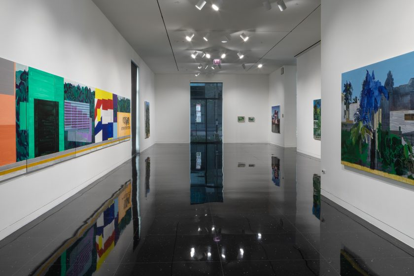 Image: An installation view of the exhibition Hurvin Anderson: Anywhere but Nowhere at The Arts Club Chicago. Several paintings can be seen hung on white walls in a gallery. Most of the paintings show green, lush foliage. The painting on the lefhand side is long and full of various bright colors. Image courtesy of The Arts Club Chicago, photo by Michael Tropea.
