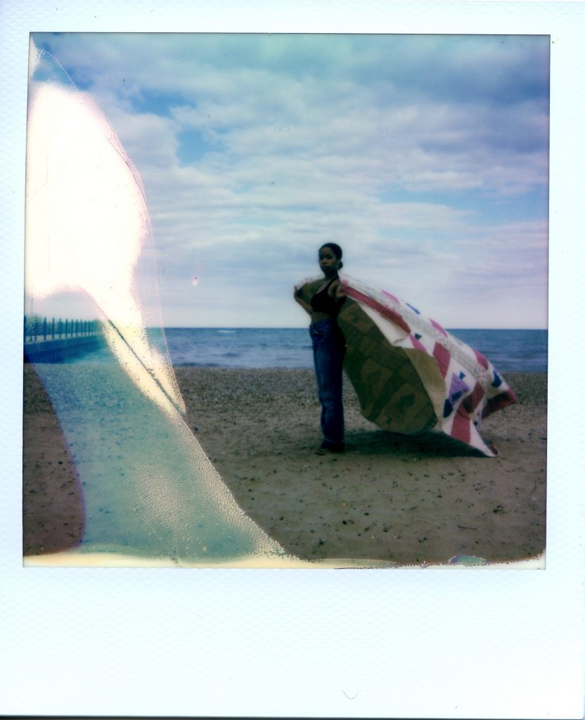 Image: A Polaroid photograph of Rikki Byrd standing on a beach in front of Lake Michigan with her body facing the left side of the photograph as she looks forward at the viewer. She holds a quilt made by her great grandmother around her shoulders like a cape while it blows in the wind. There is slight bluish coloring on the left side of the Polaroid. Jeans are vintage Levi's. Styling by row särkelä and Madeleine Le Cesne. Photo by Jared Brown.