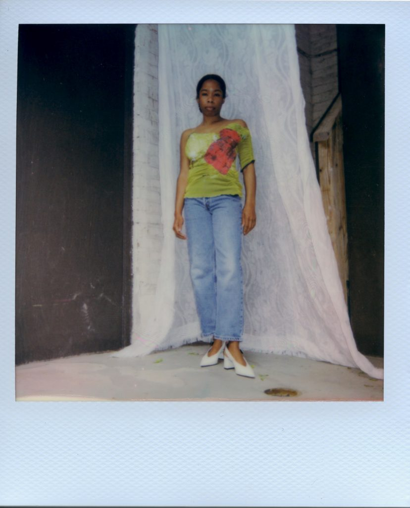 Image: A Polaroid photograph of Rikki Byrd wearing vintage blue Levi's jeans, white heels from Zara, and a greenish-yellow handmade corset top from @earthangelbaby on Depop with one sleeve and a red patch. Draped behind her is white lace. She stands while looking forward at the viewer. Styling by row särkelä and Madeleine Le Cesne. Photo by Jared Brown.