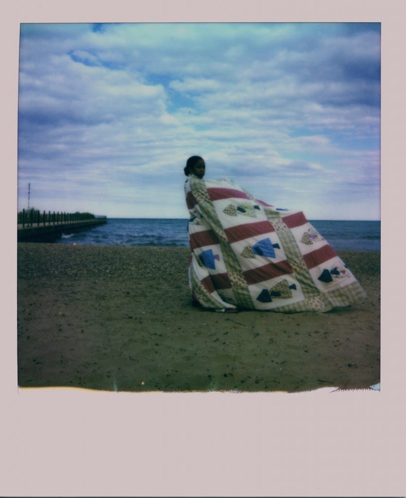 Image: A Polaroid photograph of Rikki Byrd standing on a beach in front of Lake Michigan and is wrapped in a quilt made from women in her family. She look directly at the viewer while the quilt blows in the wind. Photo by Jared Brown.