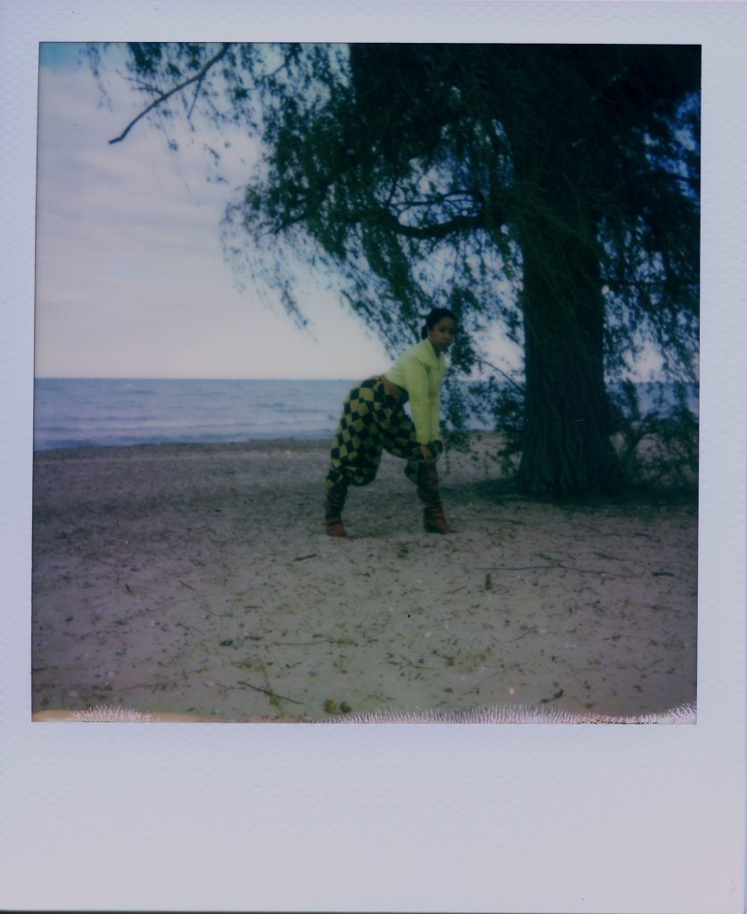 Image: A Polaroid photograph of Rikki Byrd standing on a beach while bending to the right with her hands on one knee. She wears yellow and black checkered pants, boots, and a yellow top while looking at the viewer. Photo by Jared Brown.
