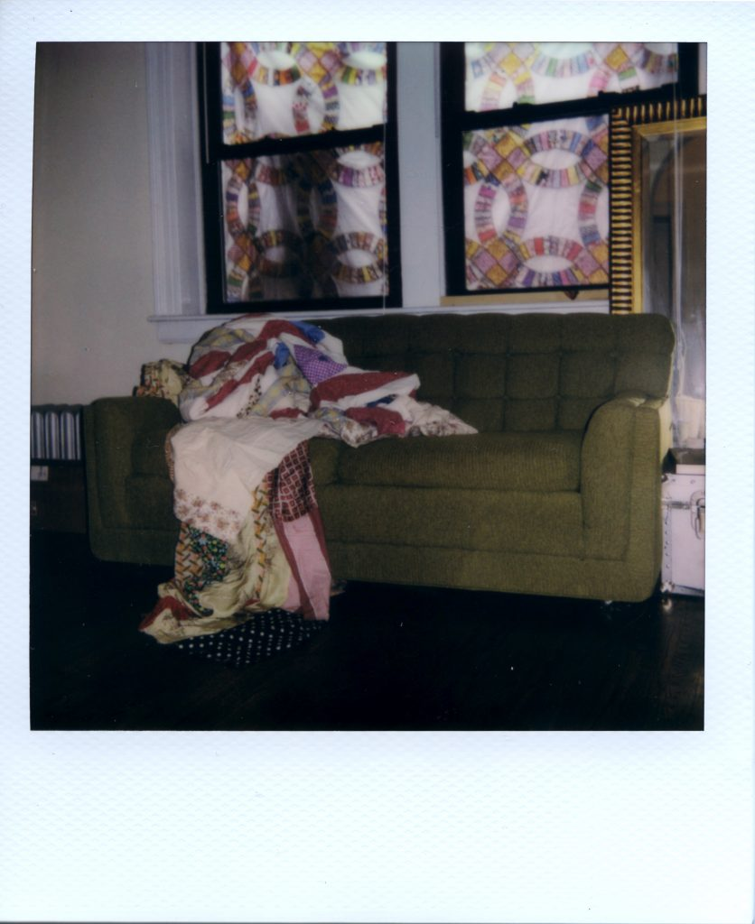 Image: A Polaroid photograph of a green couch with a quilt laying on it in Rikki Byrd's apartment. There are patches of patterned quilt pieces in the background covering the windows like a kaleidoscope. Photo by Jared Brown.