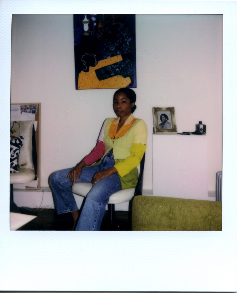 Image: A Polaroid photograph of Rikki Byrd sitting on a white chair in her apartment. She wears a blue jeans and a shirt that is magenta, yellow, green, white, and orange. Next to her sits a photo of her great-grandmother and a camera. She has her hands in her lap and looks directly at the viewer. Photo by Jared Brown.