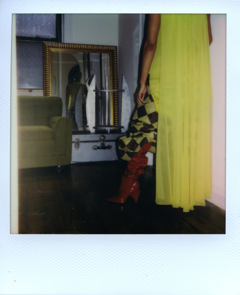 Image: A Polaroid photograph of Rikki Byrd standing in front of a mirror that is next to her green couch. The foreground shows Rikki from the back wearing red boots from Zara, green and black checkered pants from Vaquera, and a long, green dress from May's place, a vintage shop in St. Louis. The mirror shows Rikki's front. Styling by row särkelä and Madeleine Le Cesne. Photo by Jared Brown.