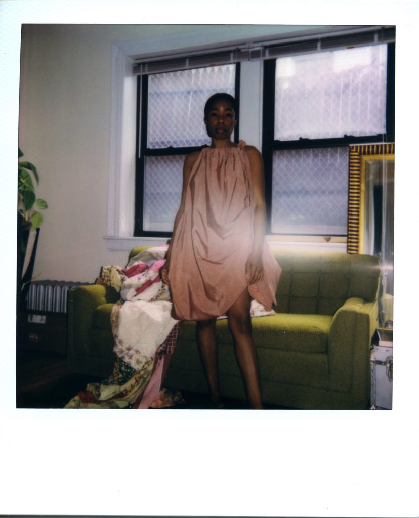 Image: A Polaroid photograph of Rikki Byrd standing in front of a window and a green couch in her apartment. A quilt lays on the couch and a mirror sits right behind the couch to the right. Rikki stands and looks straight out at the views while wearing a pale pinkish dress by Chicago-based designer Adreain Guillory. Styling by row särkelä and Madeleine Le Cesne. Photo by Jared Brown.