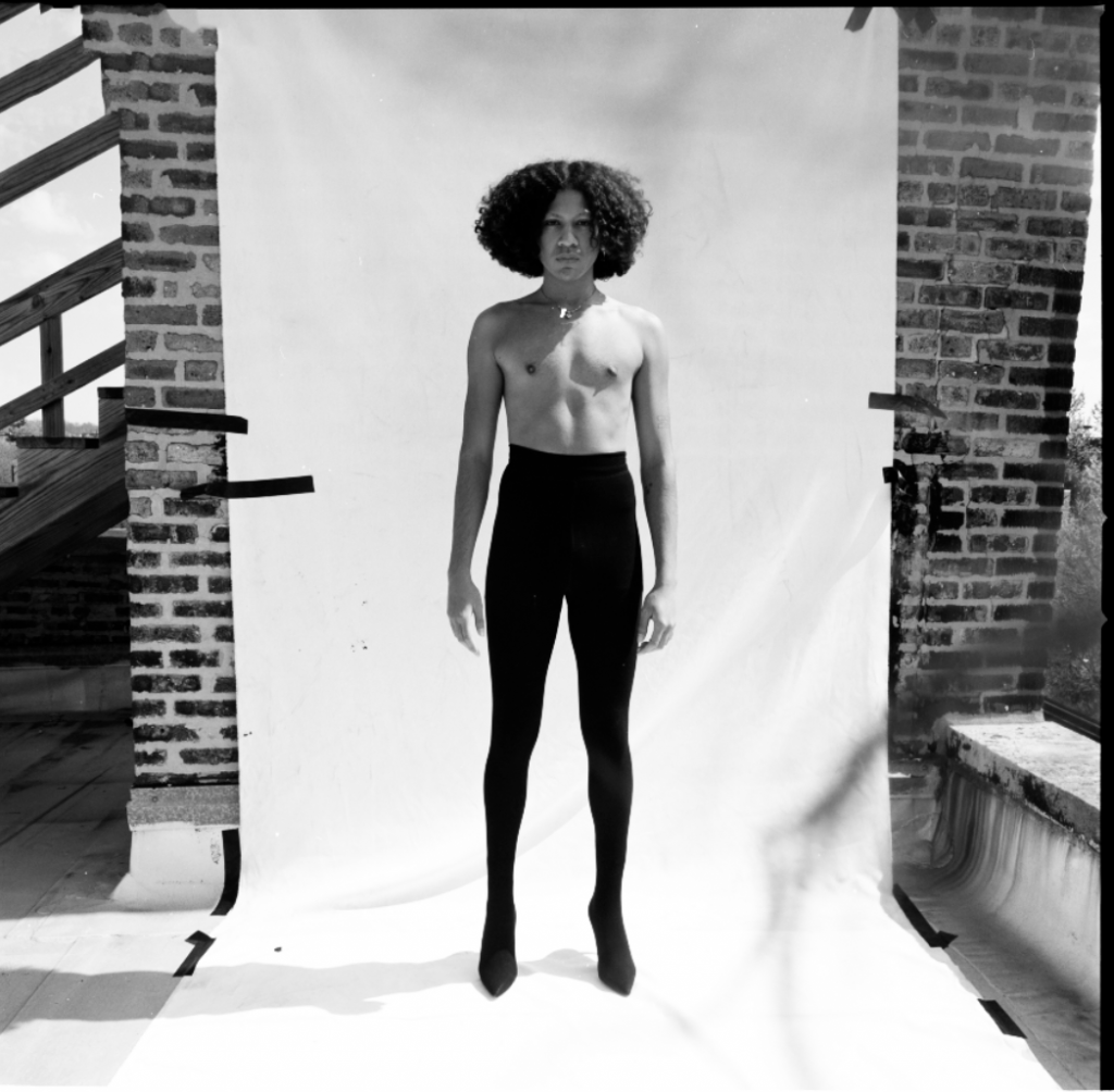 Image: A black and white photo on a roof of a person standing in front of white backdrop. VESOLO, 2021. Image by Madeline Hampton.