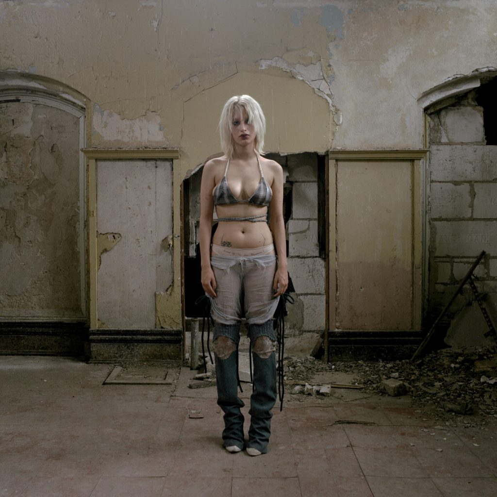 Image: A white person with white blond hair wearing deconstructed skirt, legwarmers, and bra in abandoned building. The light is yellowish and a bit eerie. Title: Genesis Lookbook for Exaltus. Year: 2021. Designer: @3xalted1. Image by Madeline Hampton.