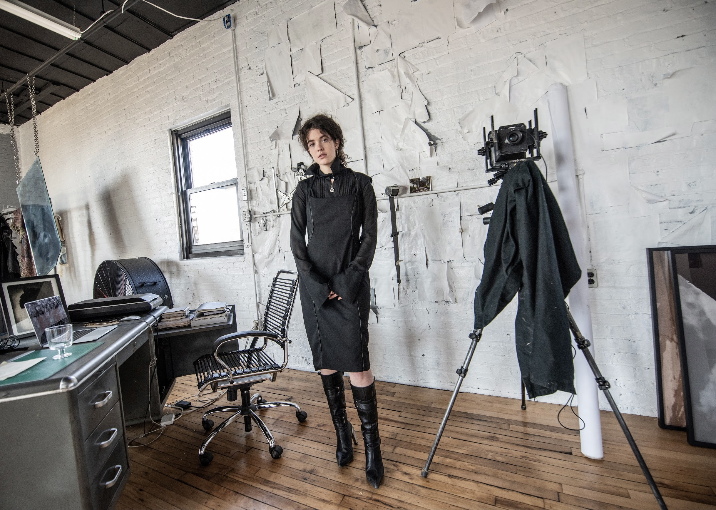 Image: A photo of Madeline Hampton in her apartment/studio. She wears a black dress and black boots and looks forward at the viewer. On the lefthand side of the photo is a window and a desk with various items sitting on top. On the righthand side is a camera on a tripod. Photo by Edvette Wilson-Jones.