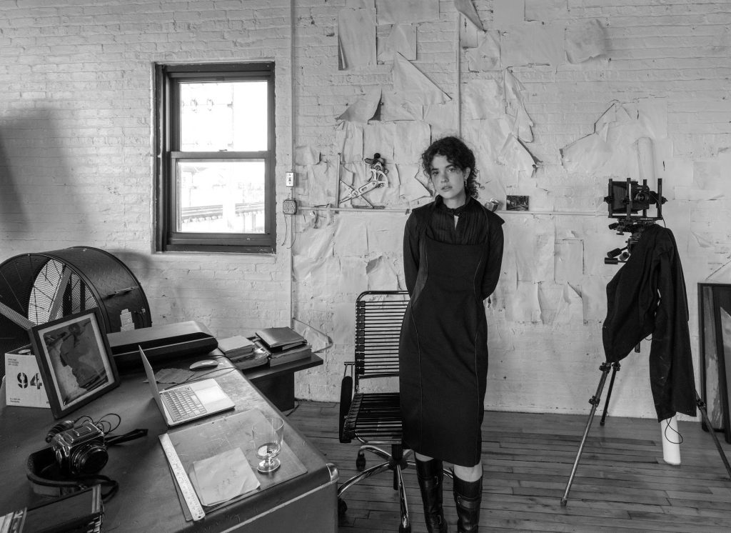 Image: A black and white photo of Madeline Hampton in her apartment/studio. She wears a black dress and black boots and looks forward at the viewer. On the lefthand side of the photo is a window and a desk with various items sitting on top. On the righthand side is a camera on a tripod. Photo by Edvette Wilson-Jones.