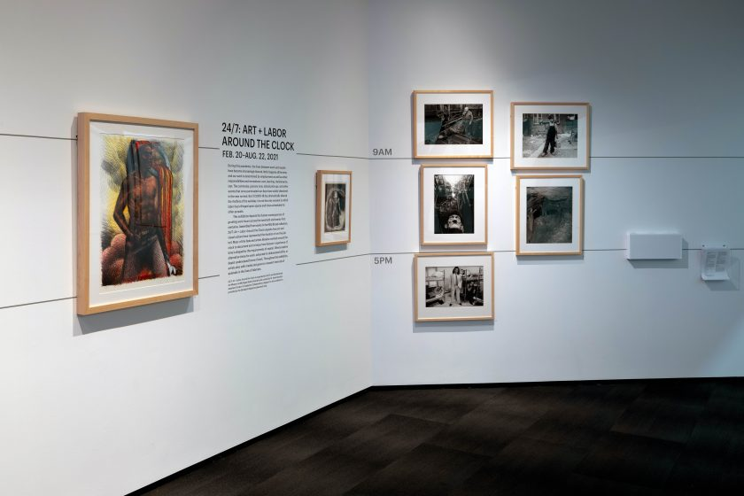 """Image: An installation view of the exhibition """"24/7: Art + Labor Around the Clock"""" at the Michigan State University Broad Museum. Seven images and a block of text describing the exhibition can be seen hung on a white wall. Two parallel lines run horizontally across the wall: the top line is marked """"9AM"""" and the bottom is marked """"5PM."""" Image courtesy of MSU Broad Museum."""