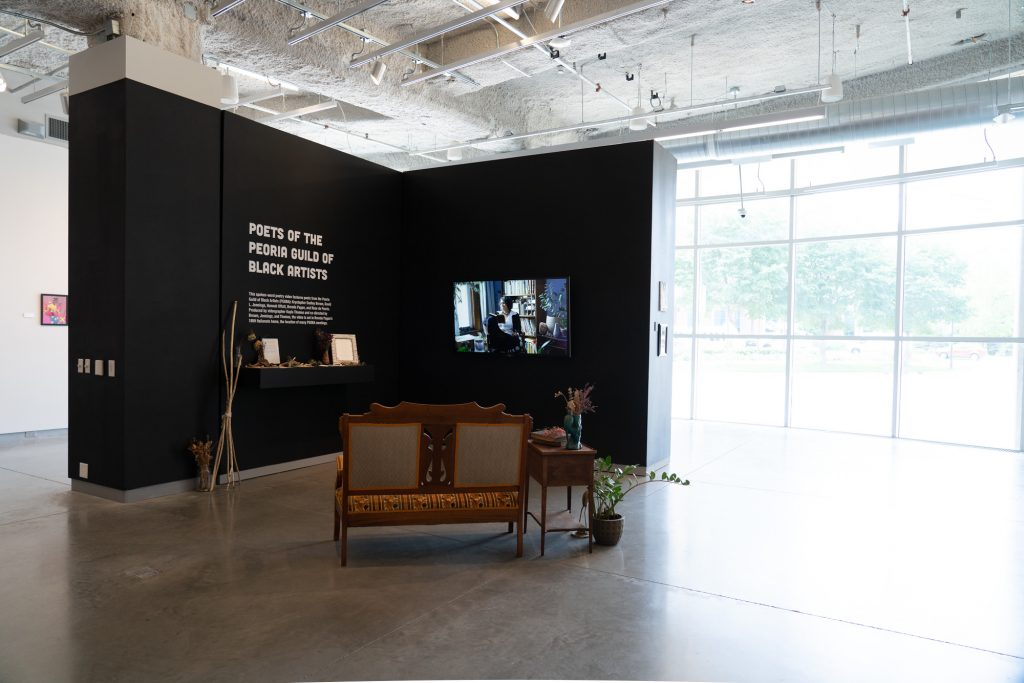 Image: An installation view of bright room with a free-standing wall at the center. The wall has a shelf holding an altar below white lettering on a black wall, and a large monitor on the adjacent wall. Just in front of the wall is a wooden upholstered seat, end table, and plants. Photo by Jessica Bingham. Courtesy of University Galleries of Illinois State University.
