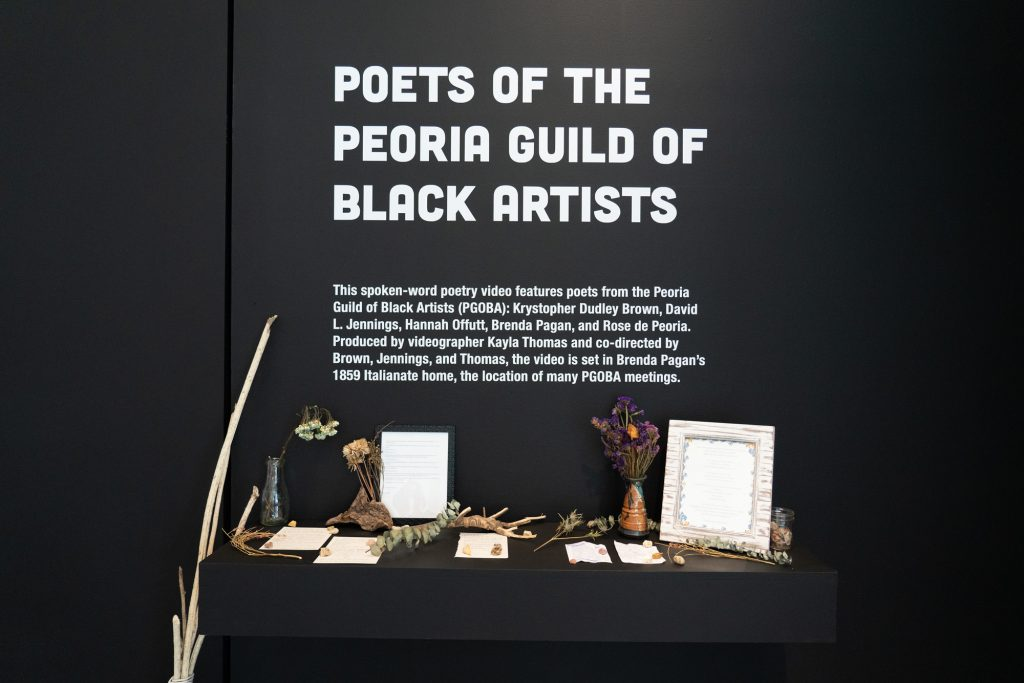 Image: An installation view of an altar of framed and loose paper resting on a shelf with dried flowers and vessels placed throughout. Above the shelf is white vinyl lettering on a black wall that reads Poets of the Peoria Guild of Black Artists with the names Krystopher Dudley Brown, David L. Jennings, Hannah Offutt, Brenda Pagan, Rose de Peoria, and Kayla Thomas underneath. Photo by Jessica Bingham. Courtesy of University Galleries of Illinois State University.