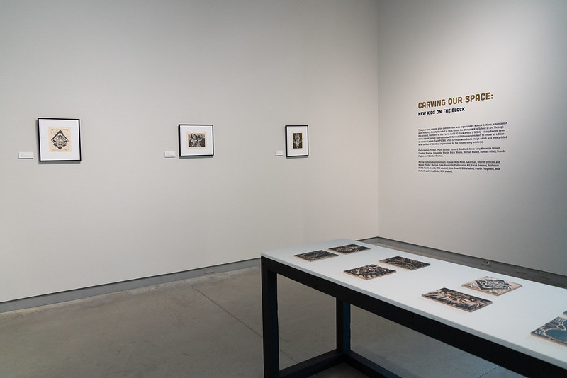 """Image: Installation view of Carving Our Space: New Kids on the Block, a portfolio project organized in collaboration with Normal Editions. The image shows three framed one-color woodcut prints on Fuji Okawara paper with a table displaying the woodblocks that these pieces and others were printed on. The adjacent wall has vinyl lettering, the largest reading """"Carving Our Space."""" Photo by Jessica Bingham. Courtesy of University Galleries of Illinois State University."""