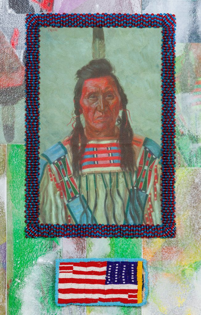 Image: Detail from Chief Pretty Eagle by Jeffrey Gibson. Towards the bottom of the image, there is a backwards American flag created from intricate beadwork. Above that is a portrait of a Native American person with intricate beadwork in blues and reds creating a frame around it. Various surface textures, colors, and glitter forms the background. Photo courtesy of the artist.