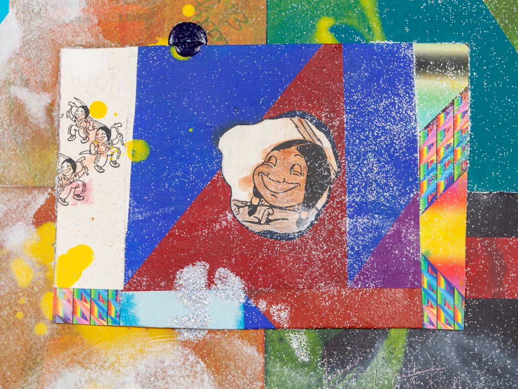 Image: Detail from Chief Pretty Eagle by Jeffrey Gibson. Created from various materials, a caricature of a Native American person sits in the center of the frame on top of geometric shapes in vivid colors. A splash of yellow paint is on the lefthand side, silver glitter lays across the entire frame. Various surface textures and colors form the background. Photo courtesy of the artist.