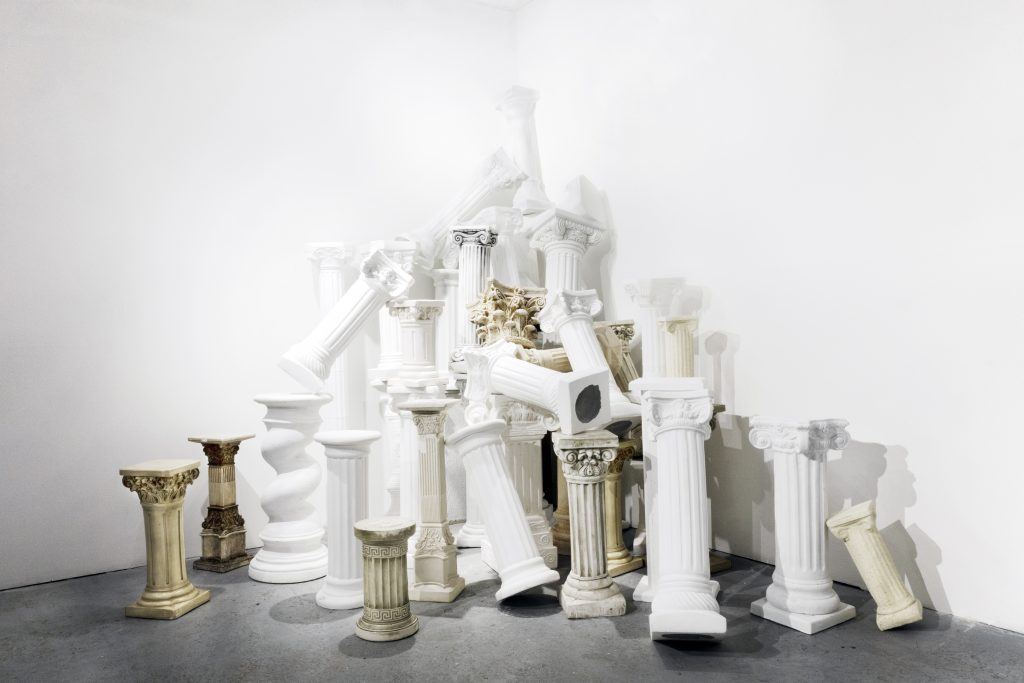"""Image: Kelly Kristin Jones, """"Orders of Empire,"""" 2020 - ongoing. Plaster, wood, concrete, fiberglass composite, polyethylene, resin. The installation is a pile of plastic, white, faux columns in the corner of 062 Gallery. Image courtesy of the artist."""