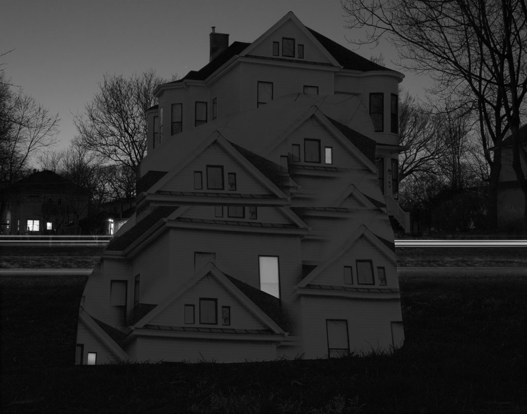 """Image: Kelly Kristin Jones, """"Untitled (From pillar to post),"""" 2021. Archival pigment print, 16in x 20 in. Edition of 3. A black and white photograph of a white house with trees and other houses behind it. Sections of the house have been duplicated and cloned in a way that is layered and overlapped. Image courtesy of the artist."""