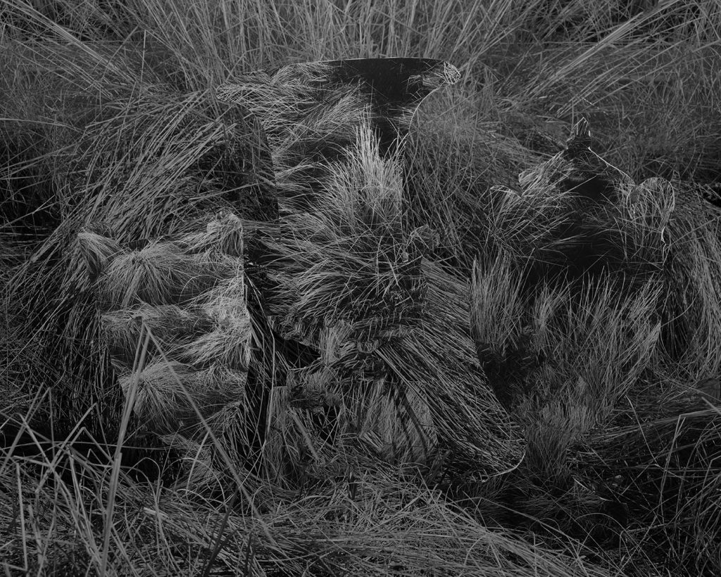 """Image: Kelly Kristin Jones, """"Untitled (Grave goods),"""" 2021. Archival pigment print, 16in x 20in. Edition of 3. A black and white photograph of long, unkempt grass. Three ghostly shapes of vases are sitting on the ground. Image courtesy of the artist."""