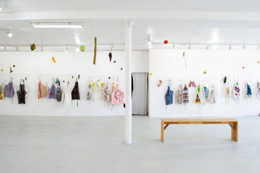 Featured image: Overview of LtdWear5 installed at the bright LVL3 gallery. The image is a landscape shot of about thirty colorful aprons and oven mitts displayed on racks on the far white wall of LVL3 gallery. In the midground of the shot is a long wooden bench and a white pole that cuts the gallery in half. Hanging from the ceiling are large plastic fruits and vegetables, including asparagus, grapes, and tomatoes. On the far wall, a large plastic baguette is hung on the wall as well offering a cheery, kitschy feeling to the gallery. Photo courtesy of LVL3.
