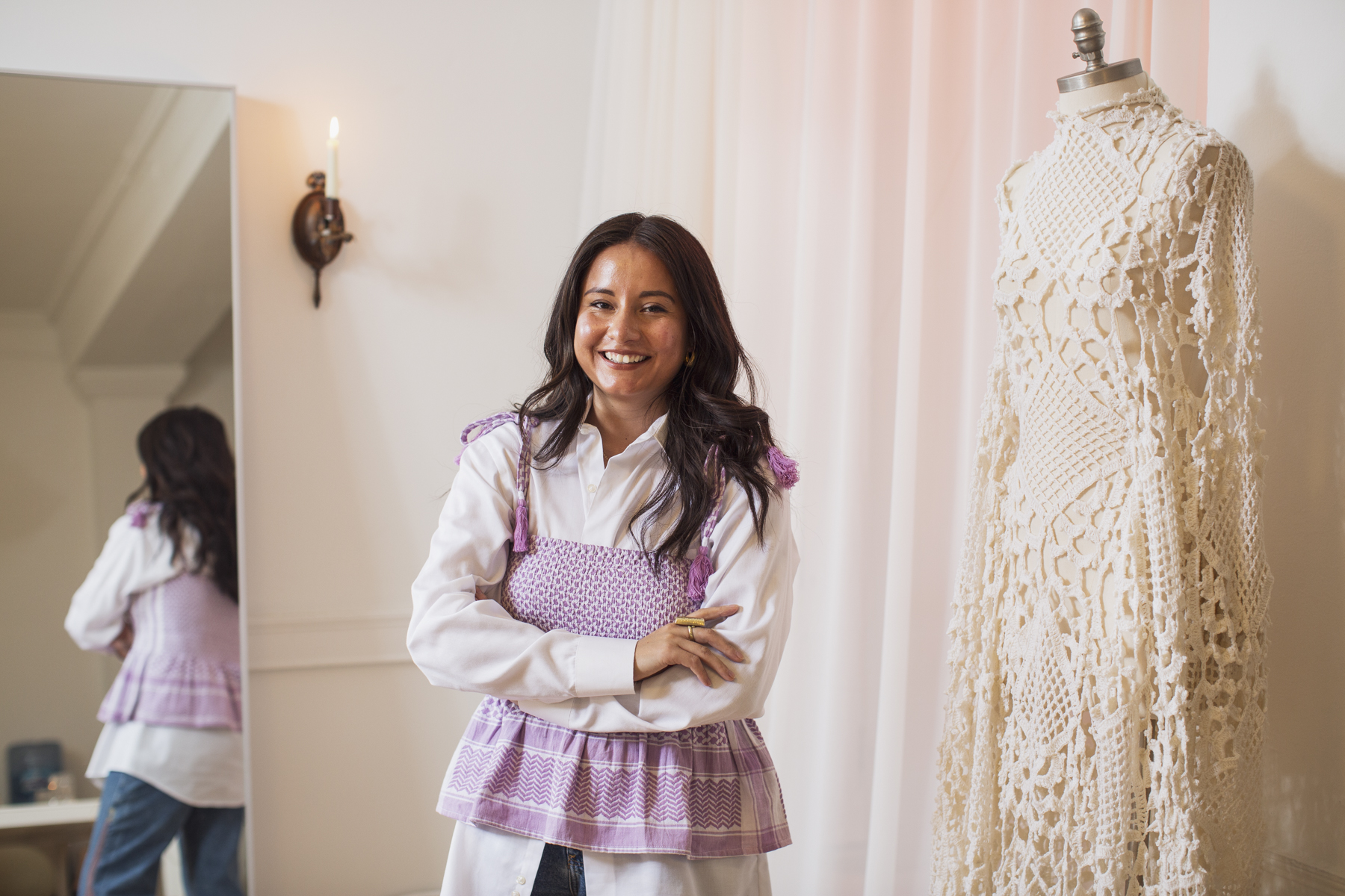 Image: Nelissa Carrillo smiles, facing the camera with her arms crossed. A mirror behind her on the left side of the image reflects her lavender peplum tank top from Cecilie Copenhagen, tied at the shoulders over a vintage white button down and blue jeans by Ciprianamía. On the right-hand side of the photograph is a floor length crochet dress on a mannequin made out of cream knits from Carrillo's grandmother's archive. Soft warm light spills out from a sconce on the back wall and reflects onto a floor-to-ceiling white curtain. Photo by Kristie Kahns.