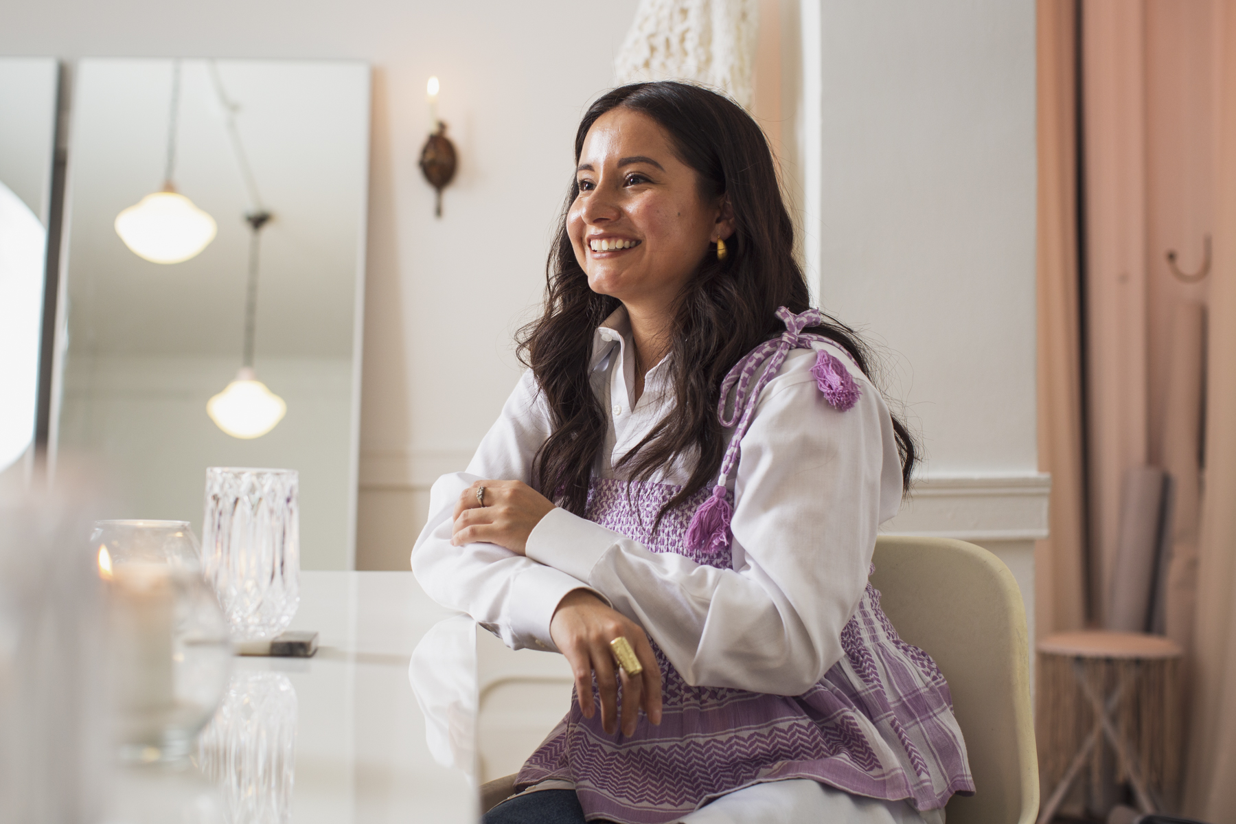 Image: Nelissa Carrillo is seated and smiling, facing away from the camera with her arms crossed and lightly resting on a reflective white table. The light casts a warm blush onto her face. The right side of the photo features peach lighting onto the dressing room of the showroom, and the left side of the photo is filled with a crystal glass, a candle, and the reflection of a pendant light in the large floor mirror. Lavender pompoms fall off of Carrillo's shoulders onto her vintage white button down, and a gold statement ring on her right hand catches light from the pendant light. Photo by Kristie Kahns.