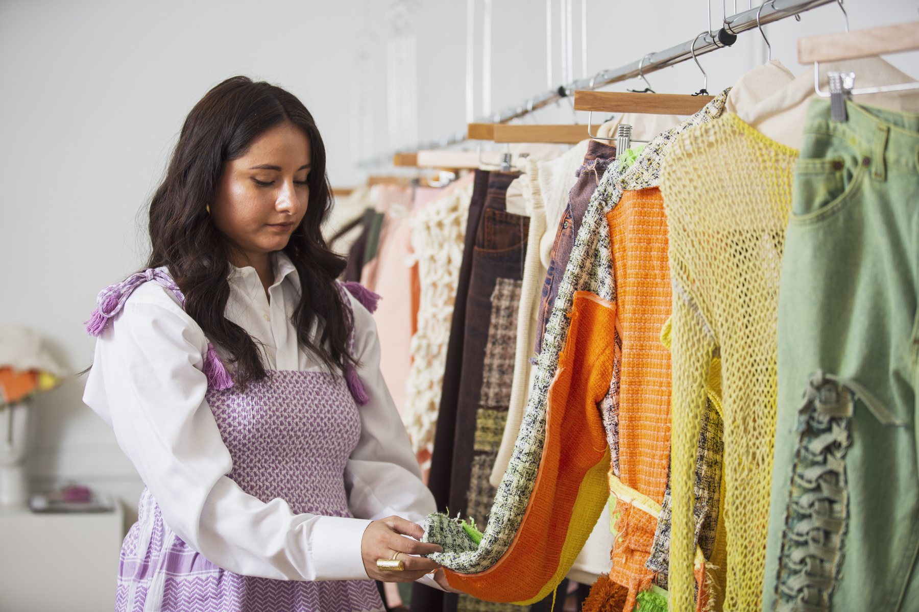 image: Nelissa Carrillo is looking down, holding the sleeve of a multi-colored jacket with a large orange patch. The jacket is on a rack of garments from Ciprianamía that take up the right side of the photo, ranging from green jeans to a yellow knit to glimpses of white sweater vests and more denim. Photo by Kristie Kahns.