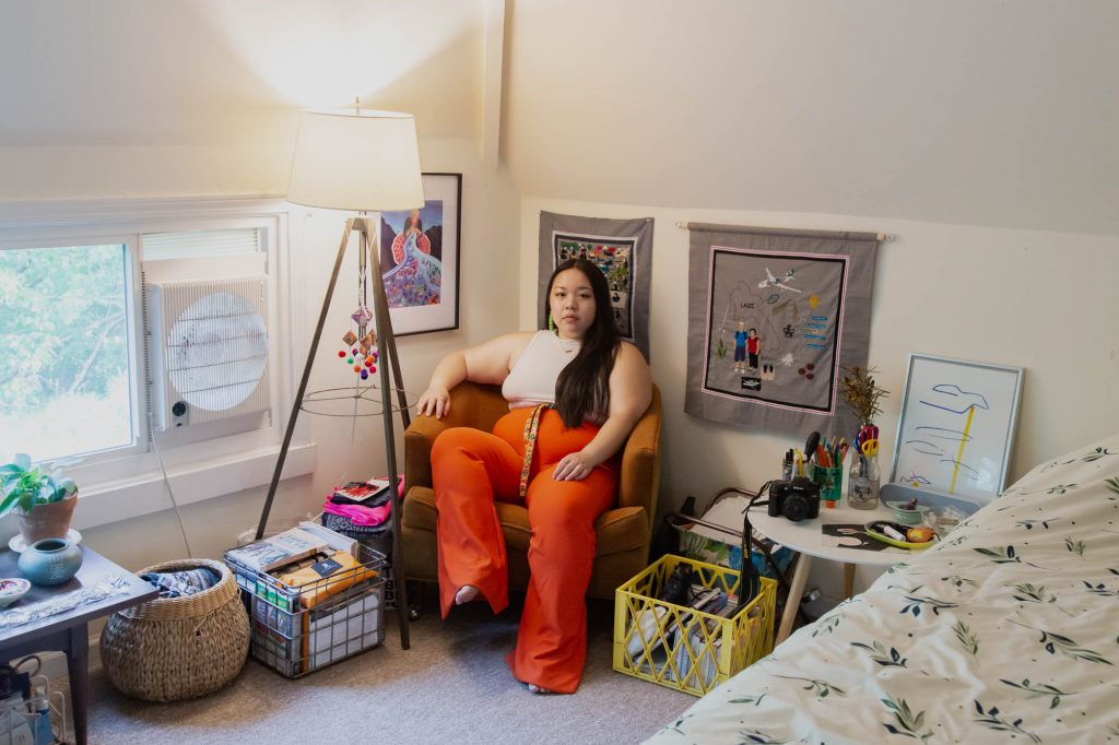 Image: A view of Tshab Her sitting in her room on an orange chair. She wears a white shirt and orange pants while looking directly at the camera. She sits amongst various containers of items. Two of her embroidery cloth pieces hang behind her. A lamp and a window are on the lefthand side of the frame. Photo by Josh Johnson.