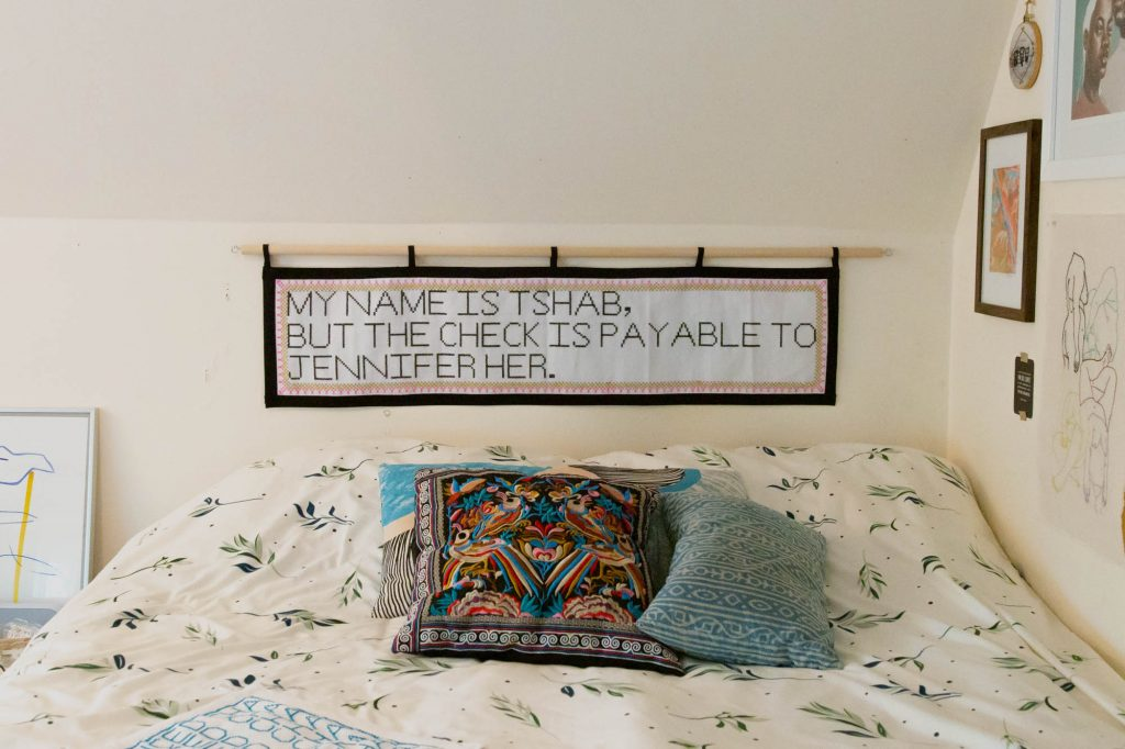 """Image: A view of Tshab Her's bedroom, showing part of her bed and pillows. On the wall to the right, various artworks hang. Above the bed hangs an embroidery piece by Tshab Her, which reads: """"MY NAME IS TSHAB, BUT THE CHECK IS PAYABLE TO JENNIFER HER."""" Photo by Josh Johnson."""