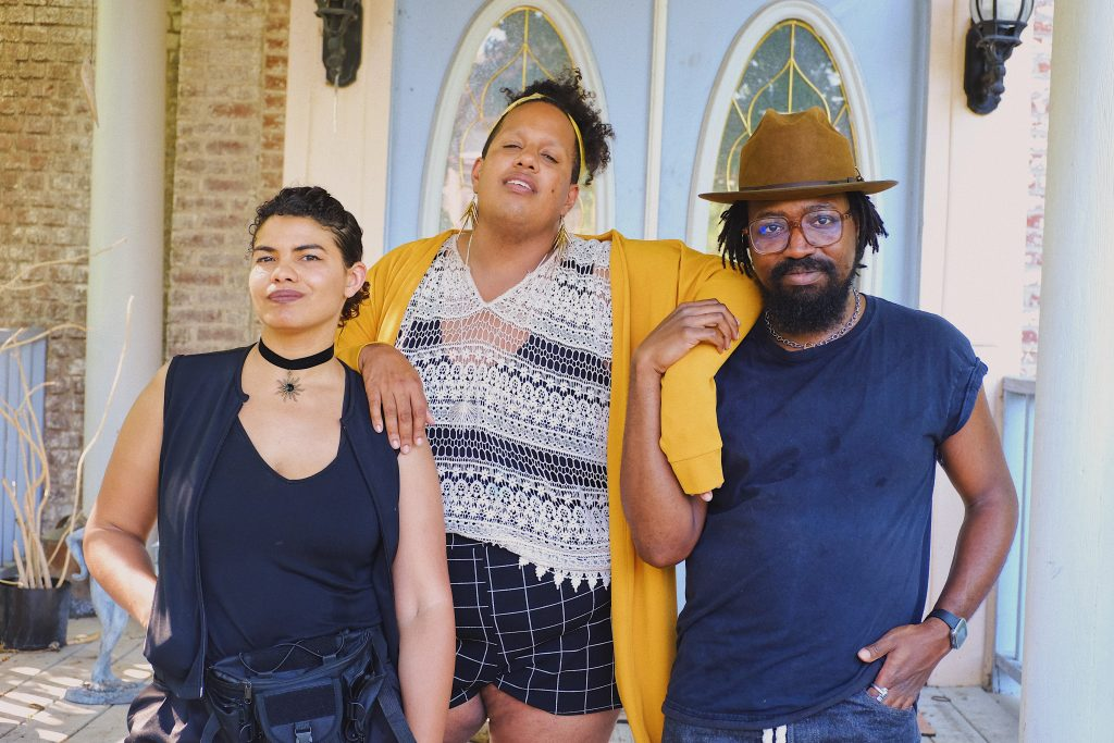 Image: Brenda Pagan, Alexander Martin, and Erick Minnis stand side-by-side, arms draped over one another or interlocked, in front of double doors, looking directly into the camera with the sun shining around them. Photo by Erick Minnis.