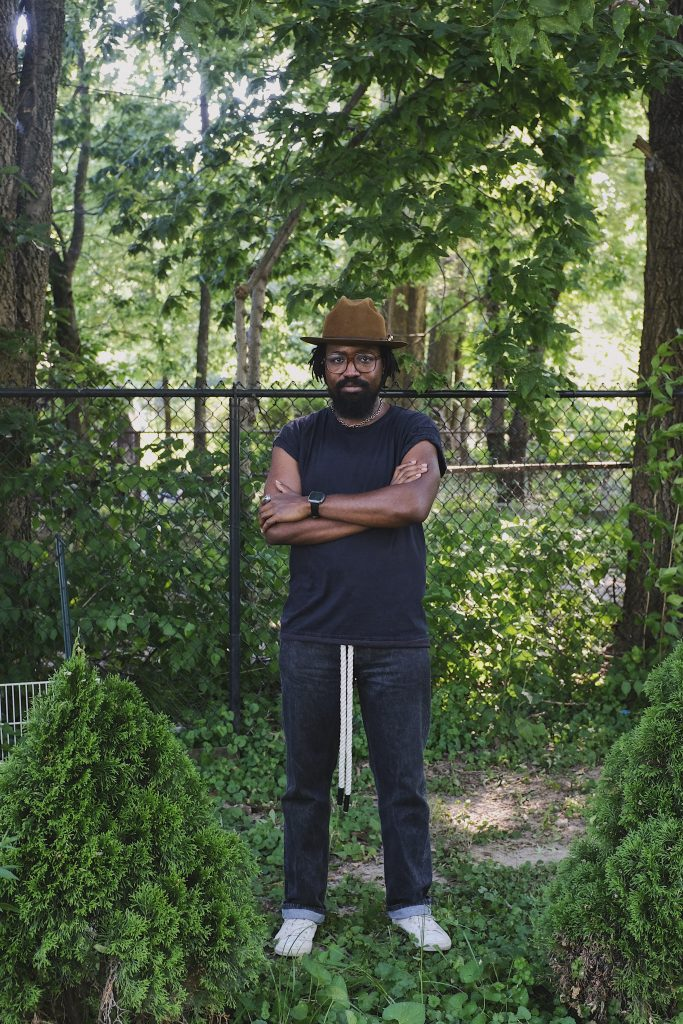 Image: A portrait of  Erick Minnis dressed in a dark top, jeans, a brown hat, and glasses, standing in the middle of greenery with arms folded. Photo by Erick Minnis.