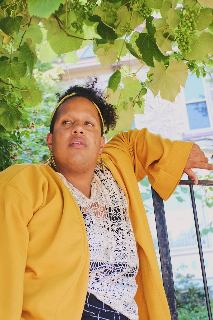 Image: A portrait of Alexander Martin dressed in a yellow jacket, white top, and dark striped shorts, arm resting on the top of a metal fence and standing under a grape vine. Photo by Erick Minnis.