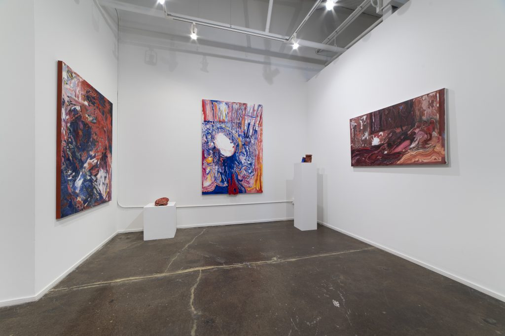 Image: An installation view of three paintings against a white wall with three-dimensional pieces sitting on a white pedestal on each side of the middle painting. The painting to the left uses large, gestural strokes in dark blues and reds. The painting in the middle shows a group of people standing in a circle with reds and blues. The painting on the right is the darkest of the three, using mostly dark maroons and burgundy hues. All work is by Karen Dana Cohen. Image courtesy of the artist.