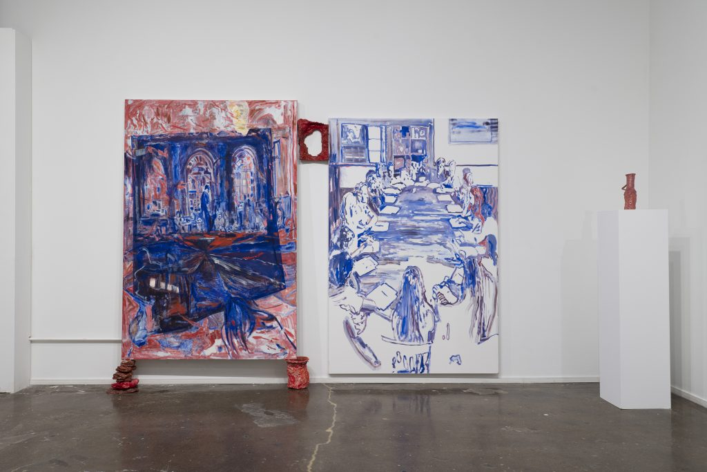 Image: An installation view of two paintings against a white wall with a three-dimensional piece sitting on a white pedestal to the very right of the frame. The painting to the left uses large, gestural strokes in dark blues and reds. The painting on the right shows a group of people sitting at a long table. The painting is mostly white and blue with hints of red. All work is by Karen Dana Cohen. Image courtesy of the artist.