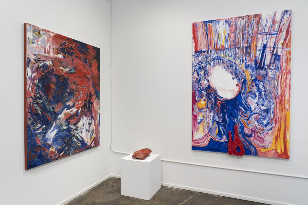 Image: An installation view of two paintings hanging on a white wall with a three-dimensional piece sitting on a white pedestal in the foreground. The painting to the left uses large, gestural strokes in dark blues and reds. The painting on the right shows a group of people in a circle with painterly strokes in reds and blues. All work is by Karen Dana Cohen. Image courtesy of the artist.